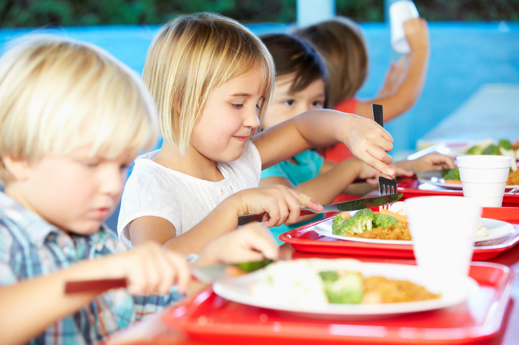 Elementary Pupils Enjoying Healthy Lunch In Cafeteria Using Knife And Fork